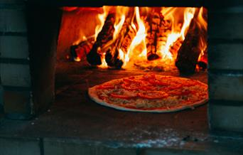 Enjoy tasty wood-fired pizzas